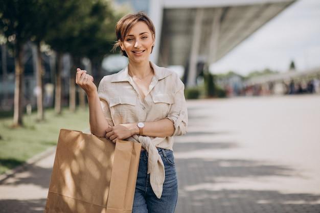 Молодая женщина с хозяйственными сумками