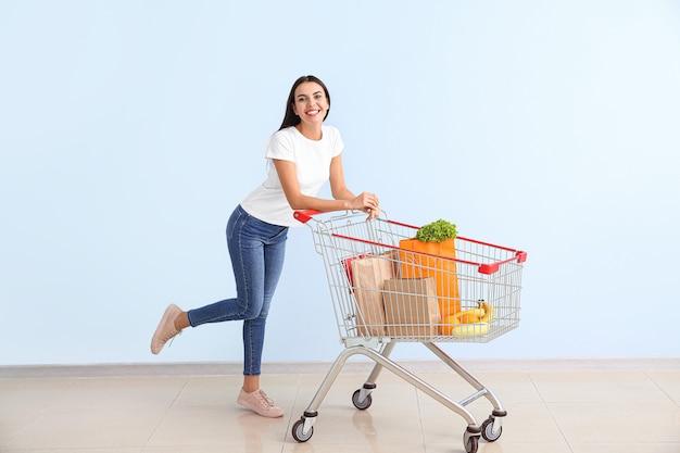 Молодая женщина с корзиной возле цветной стены