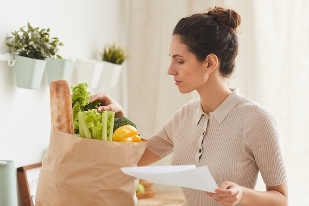 Young woman with shopping list bringing fresh vegetables in paper bag to home