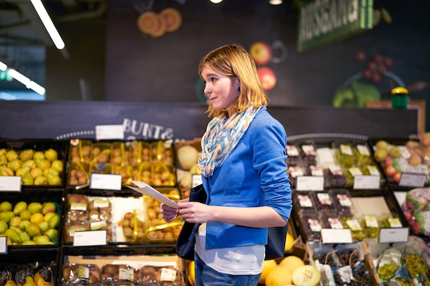 Young woman with shopping list in shop