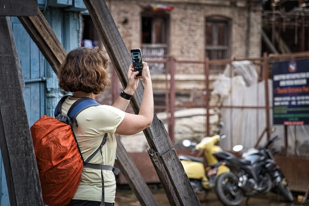Young woman with short brunette hair photographing with her smartphone a hindu temple in nepal, asia. orange backpack with water proof cover