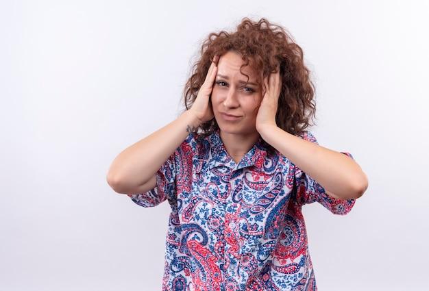 Giovane donna con capelli ricci corti in camicia colorata stressata e preoccupata di toccare la sua testa con le mani in piedi sul muro bianco