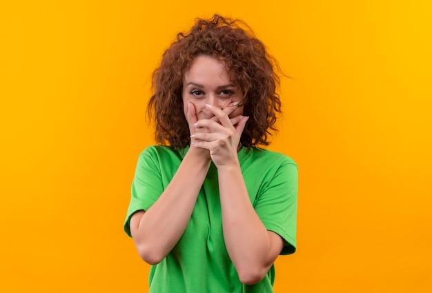 Giovane donna con capelli ricci corti in maglietta verde che sembra sorpresa che copre la bocca con le mani in piedi