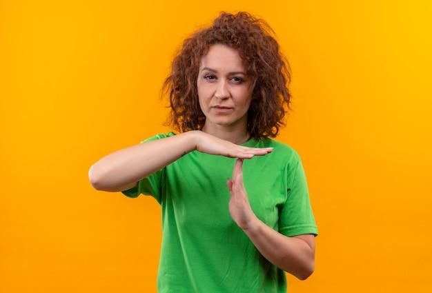 Giovane donna con i capelli ricci corti in maglietta verde che sembra stanca che fa gesto di time out con le mani in piedi