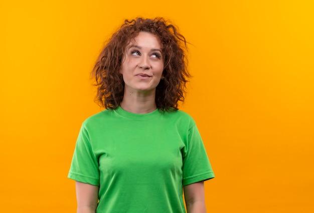 Giovane donna con i capelli ricci corti in maglietta verde che osserva in su con lo sguardo sognante in piedi