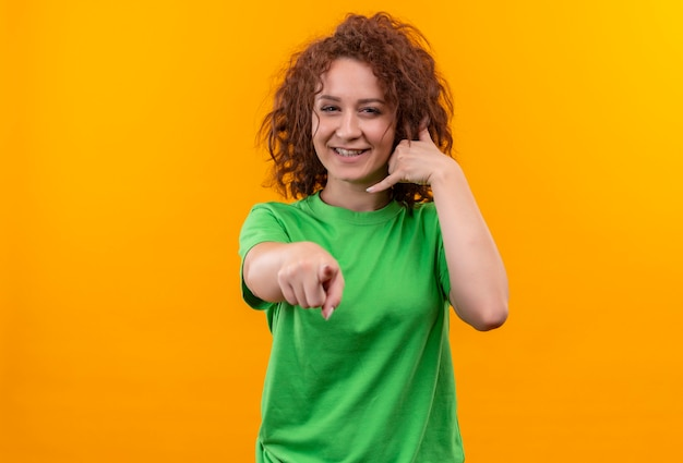 Young woman with short curly hair in green t-shirt making call me gesture pointing with finger at front
