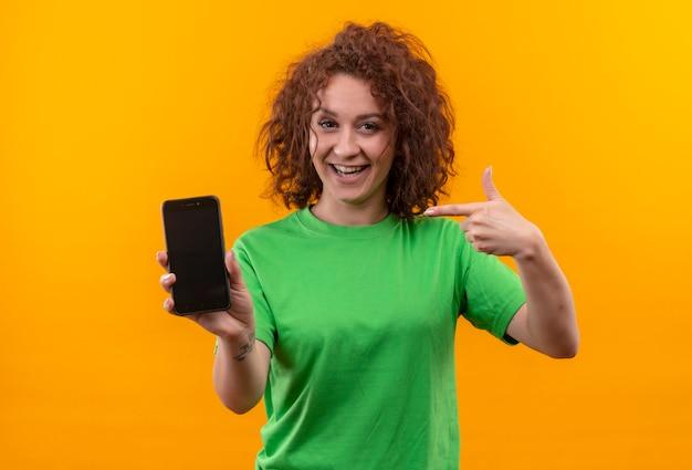 Giovane donna con i capelli ricci corti in maglietta verde che mostra lo smartphone che punta con il dito sorridendo allegramente in piedi sopra la parete arancione