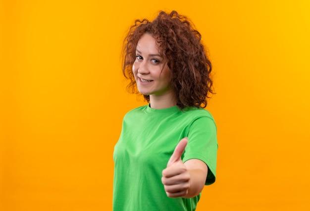 Giovane donna con capelli ricci corti in maglietta verde che sorride allegramente mostrando i pollici in su in piedi sopra la parete arancione