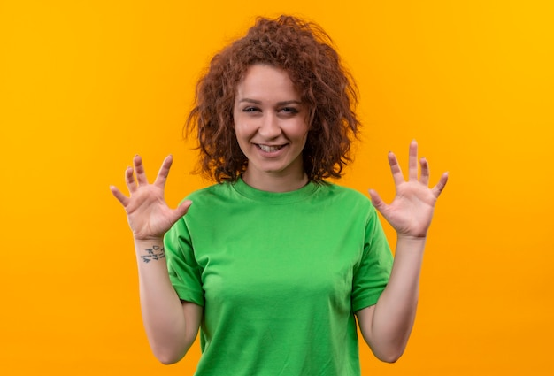 Young woman with short curly hair in green t-shirt smiling making cat claws gesture standing over orange wall