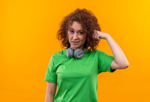 Giovane donna con i capelli ricci corti in maglietta verde con le cuffie che sembrano confuse indicando con il dito il suo tempio in piedi sopra la parete arancione