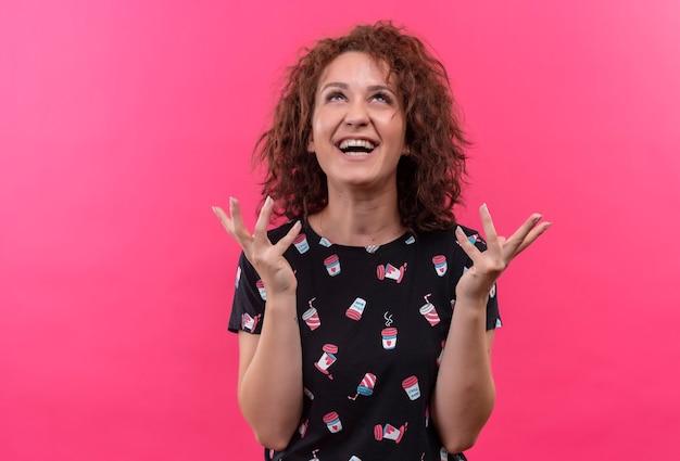 ピンクの壁の上に立っている上げられた手で幸せで興奮している短い巻き毛の若い女性