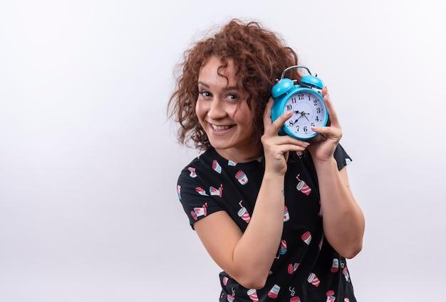 Молодая женщина с короткими вьющимися волосами держит будильник, весело улыбаясь, стоя над белой стеной