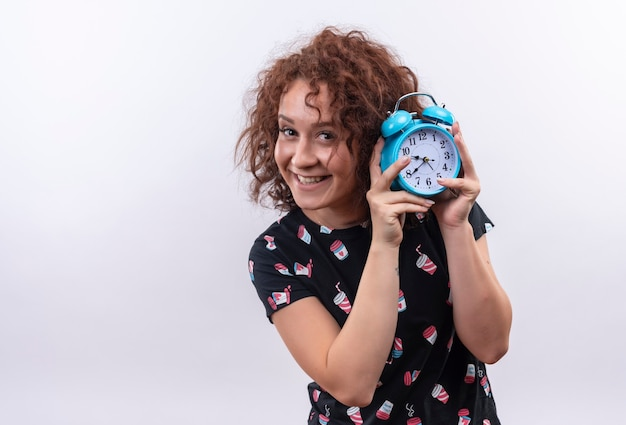 Young woman with short curly hair holding alarm clock smiling cheerfully standing over white wall