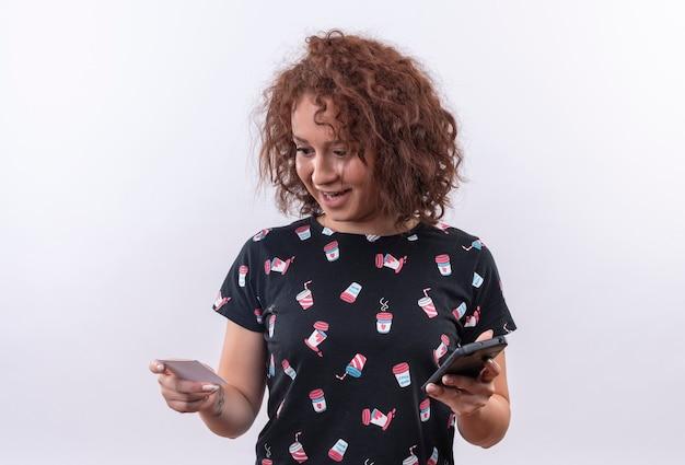 Молодая женщина с короткими вьющимися волосами, держащая кредитную карту и смартфон, выглядит удивленной и счастливой, стоя над белой стеной