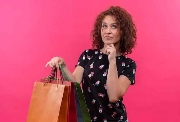 ピンクの壁の上に立って選択をしようとしている顔に物思いにふける表情で見上げる紙袋を保持している短い巻き毛の若い女性