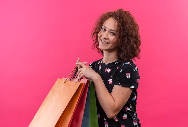 ピンクの壁の上に元気に幸せで前向きに立って笑っている紙袋を保持している短い巻き毛の若い女性