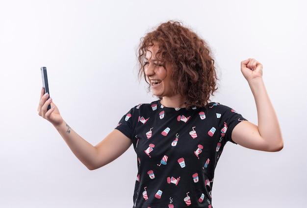 Giovane donna con i capelli ricci corti che tiene il pugno di serraggio dello smartphone felice ed emozionato che si rallegra del suo successo in piedi sopra il muro bianco