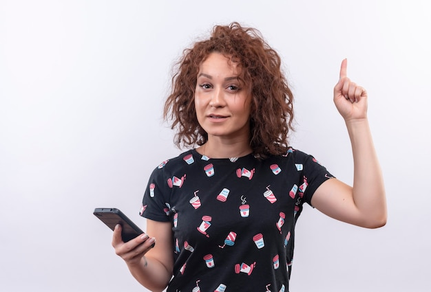 Young woman with short curly hair holding smartphone pointing up with index finger looking smart having great idea standing over white wall