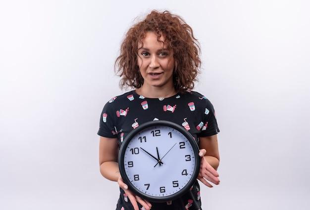 白い壁の上に立って驚いて見える壁時計を保持している短い巻き毛の若い女性