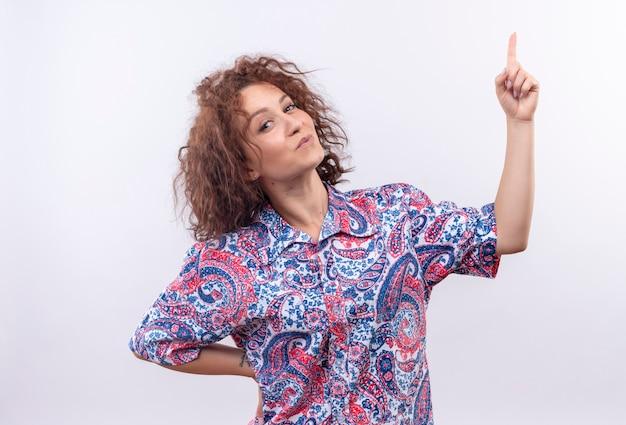Молодая женщина с короткими вьющимися волосами в яркой рубашке счастлива и позитивно смотрит вверх с пальцами, стоящими над белой стеной