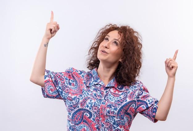 カラフルなシャツの短い巻き毛の若い女性は、白い壁の上に立っている指で上向きと上向きに幸せで前向きに