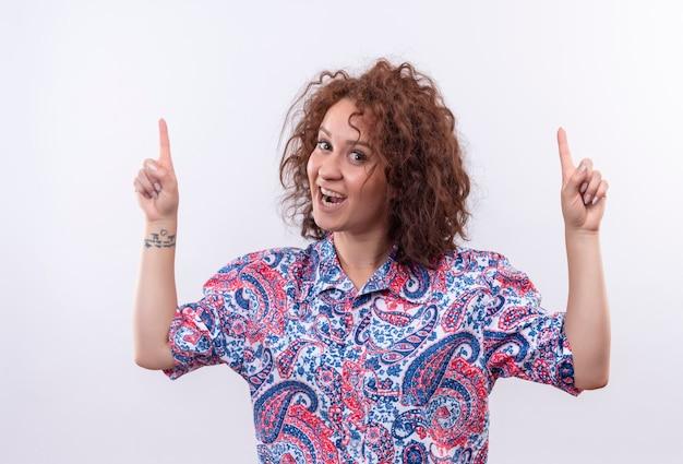 カラフルなシャツの短い巻き毛の若い女性は、白い壁の上に立っている指で広く見て、上向きに笑顔で幸せで前向きな笑顔