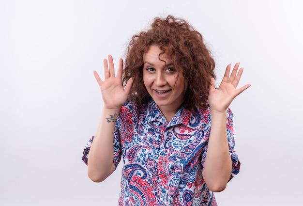 白い壁の上に立っている顔の近くに手のひらを持って元気に笑って楽しんで楽しんでいるカラフルなシャツの短い巻き毛の若い女性