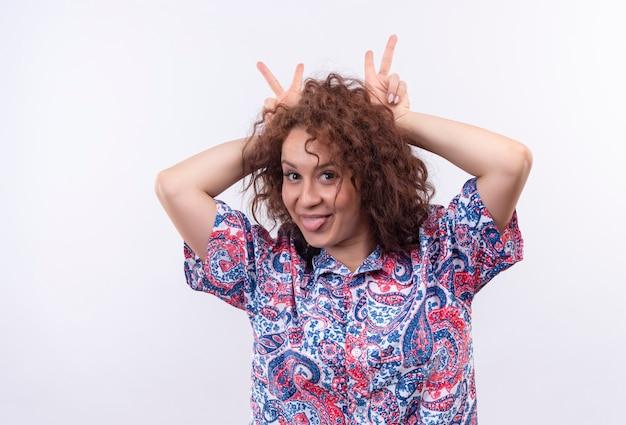 白い壁の上の指で彼女の頭の上に角を模倣して舌を突き出すのを楽しんでいるカラフルなシャツの短い巻き毛の若い女性