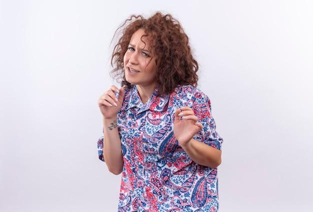 白い壁の上に立っているうんざりした表情で手で防衛ジェスチャーを作るカラフルなシャツの短い巻き毛の若い女性