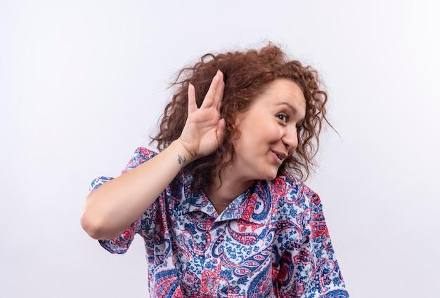 白い壁越しに誰かの会話を聴こうとしている耳の近くの手で立っているカラフルなシャツの短い巻き毛の若い女性
