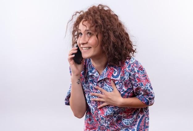 白い壁の上に立っている顔に恥ずかしがり屋の笑顔で携帯電話で話しているカラフルなシャツの短い巻き毛の若い女性