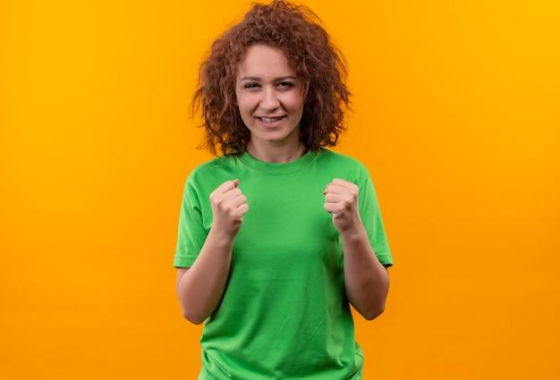 オレンジ色の壁の上に立って幸せで興奮した拳を握りしめている緑のtシャツの短い巻き毛の若い女性