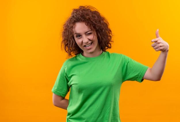 Молодая женщина с короткими вьющимися волосами в зеленой футболке счастлива и позитивно подмигивает, показывая пальцы вверх, стоя над оранжевой стеной