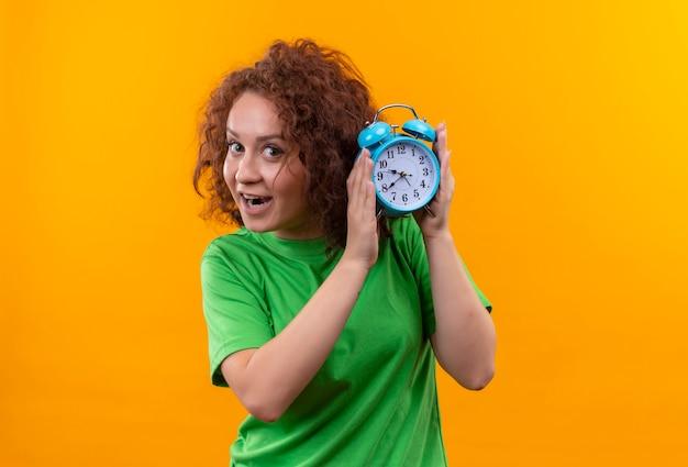 オレンジ色の壁の上に立って幸せで驚いた目覚まし時計を保持している緑のtシャツの短い巻き毛の若い女性