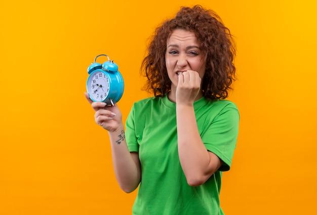 Молодая женщина с короткими вьющимися волосами в зеленой футболке с будильником в стрессе и нервно кусает ногти, стоя над оранжевой стеной