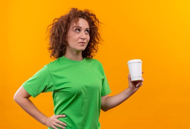 Молодая женщина с короткими вьющимися волосами в зеленой футболке держит чашку кофе, глядя в сторону с задумчивым выражением лица, стоя над оранжевой стеной