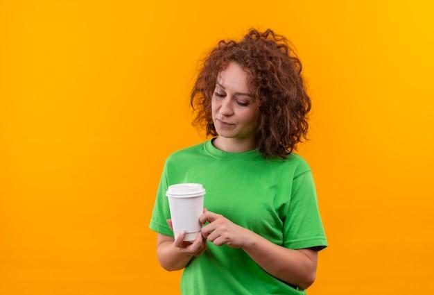オレンジ色の壁の上に立っている顔に悲しい表情でそれを見てコーヒーカップを保持している緑のtシャツの短い巻き毛の若い女性