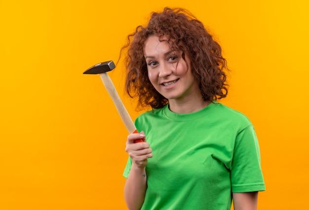 Молодая женщина с короткими вьющимися волосами в зеленой футболке держит молоток, весело улыбаясь стоя