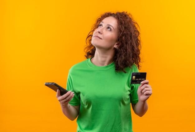선택 서 만들기 위해 노력하는 얼굴에 잠겨있는 표정으로 올려 두 스마트 폰을 들고 녹색 티셔츠에 짧은 곱슬 머리를 가진 젊은 여자