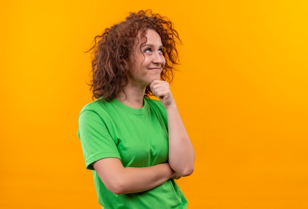 꿈꾸는듯한 표정으로 옆으로 보이는 녹색 티셔츠에 짧은 곱슬 머리를 가진 젊은 여자