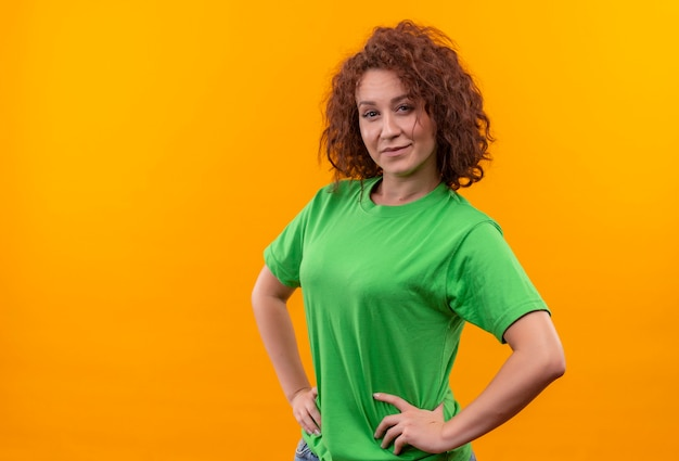 立っている顔に笑顔で自信を持って見える緑のtシャツの短い巻き毛の若い女性