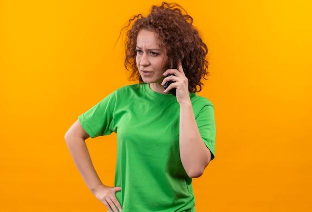 立っている携帯電話で話している間混乱し、非常に心配そうに見える緑色のtシャツの短い巻き毛の若い女性