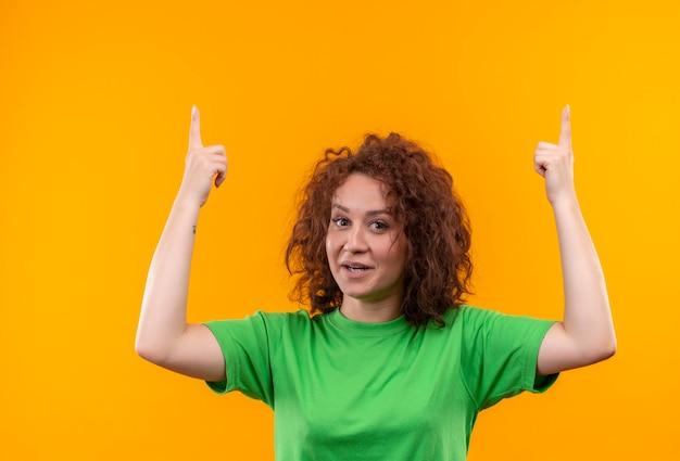 緑のtシャツの短い巻き毛の若い女性が立っている素晴らしいアイデアを持って指で指して笑顔を探しています