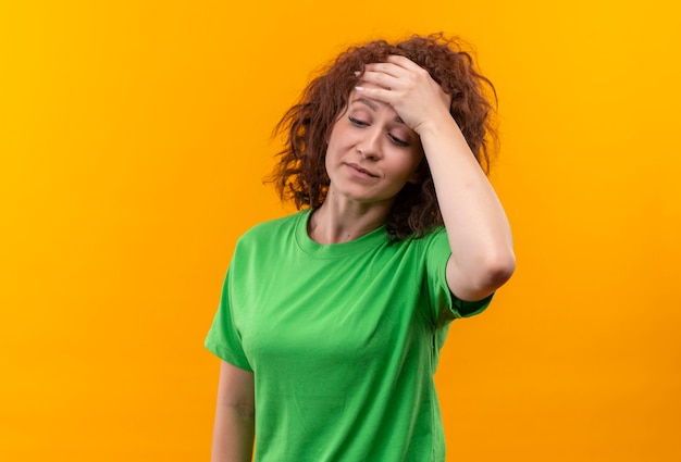 Молодая женщина с короткими вьющимися волосами в зеленой футболке выглядит усталой и скучающей с рукой на голове с головной болью стоя