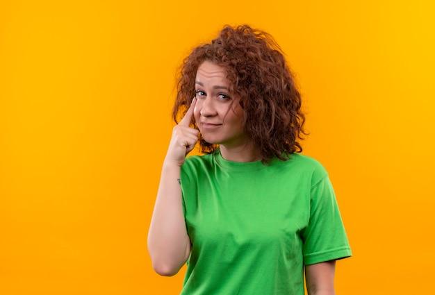オレンジ色の壁の上に立ってジェスチャーを見て人差し指で指している緑のtシャツの短い巻き毛の若い女性