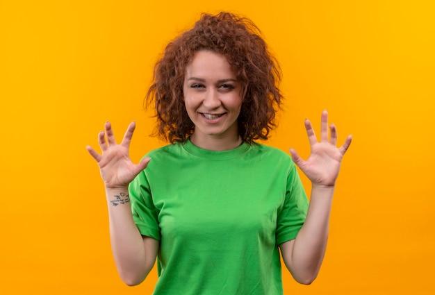Молодая женщина с короткими вьющимися волосами в зеленой футболке улыбается, делая жест кошачьих когтей, стоя над оранжевой стеной