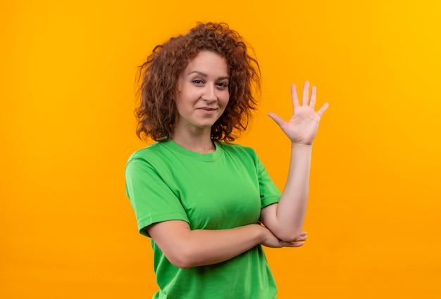 オレンジ色の壁の上に立っている手で手を振って笑っている緑のtシャツの短い巻き毛の若い女性