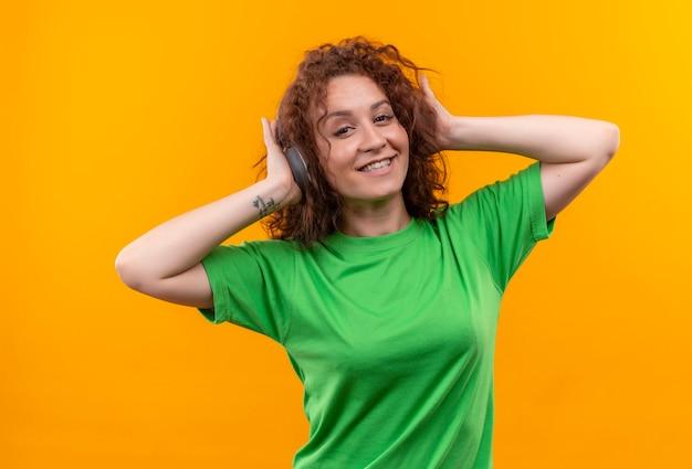 オレンジ色の壁の上に元気に立って笑顔で彼女のお気に入りの音楽を楽しんでいるヘッドフォンと緑のtシャツの短い巻き毛の若い女性