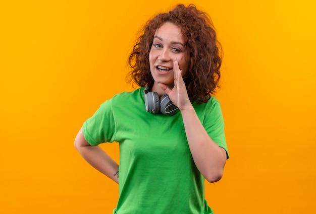 オレンジ色の壁の上に立っている口の近くの手で秘密を語るヘッドフォンと緑のtシャツの短い巻き毛の若い女性