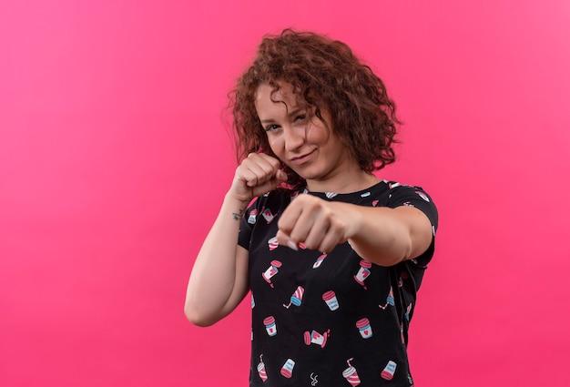 ピンクの壁の上に立っているくいしばられた握りこぶしでボクサーのようにポーズをとって見える短い巻き毛の若い女性